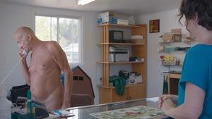 Un homme nu répond au téléphone sous le regard d'une dame dans un bureau.