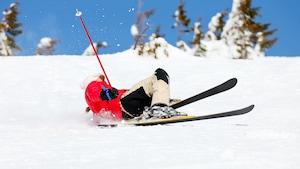 Une skieuse fait une chute sur une pente enneigée.