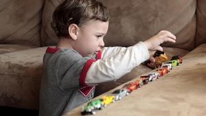 Un enfant autiste joue avec des voiturettes.