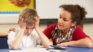 Une femme parle à un enfant qui semble tendu avec sa main sur son épaule.