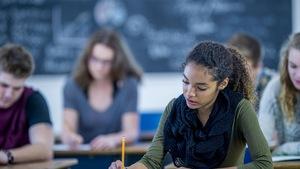 Une étudiante passe un examen en classe.