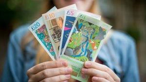 Une femme tient dans ses mains des billets de 1, 5, 10 et 20 livres de Bristol.
