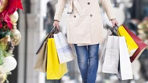 Une femme marche avec ses nombreuses emplettes de Noël.
