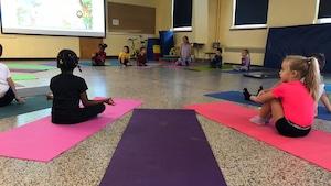 Des enfants de la maternelle à la 6e année assis sur le sol d'une classe