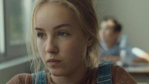 une jeune fille blonde regarde au loin.