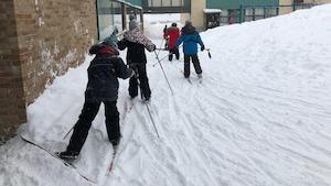 Un groupe de jeunes étudiants pratiquent le ski de fond dans la cour de l'école