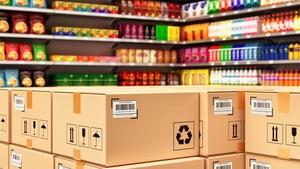 Des étagères d'épicerie remplies de produits devant lesquels sont déposées des boites de livraison en carton.