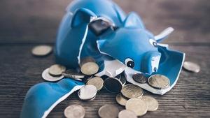 Des pièces de monnaie sortent d'un cochon tirelire cassé.