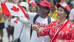Deux personnes habillées de rouge et blanc agitent des drapeaux canadiens lors d'une parade de la fête du Canada à Montréal.