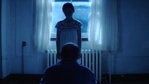 Une enfant fait face à un homme dans une pièce sombre.