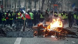 Des manifestants derrière des barricades faites avec du mobilier urbain.