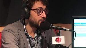 Gaël Perry est devant un micro dans le studio radio de Phare Ouest