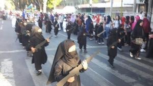 De jeunes filles défilent habillées de noir de la tête au pied avec une arme en carton dans les mains.