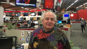 Un homme est photographié dans une salle de nouvelles.