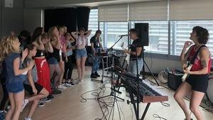 Deux femmes chantent et jouent de la guitare devant un groupe d'une vingtaine de jeunes filles.