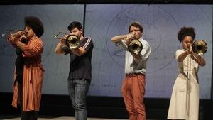 4 jeunes Cubains jouant du trombone sur scène, devant une projection d'une carte géographique ancienne