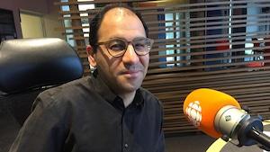 Guiy Lazure en studio devant un micro.