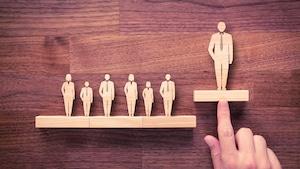 Une sculpture de bois représentant un homme portant une cravate est poussée par un doigt vers le haut. Cela fait en sorte que l'homme en cravate est plus haut que les autres personnages en bois qui sont placés à sa droite et qui représentent des hommes et des femmes de différentes grosseurs.