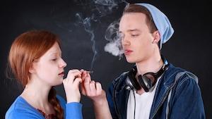 Une jeune fille et un jeune garçon échangent un joint de cannabis.