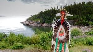 Homme vêtu d'un costume traditionnel autochtone près du fleuve St-Laurent, à Essipit