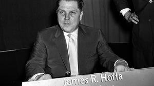 Photo en noir et blanc d'un homme assis devant une affiche avec l'inscription James R. Hoffa Teamsters.