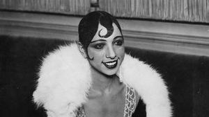 Photo en noir et blanc d'une femme souriante qui porte de la fourrure sur ses épaules.
