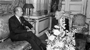 Photo en noir et blanc de deux hommes assis qui discutent.