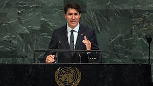 Justin Trudeau s'adresse aux délégués de l'ONU devant un mur en marbre.