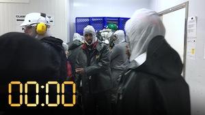 Des travailleurs enfilent leur tenue de travail dans une usine.