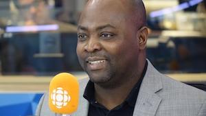 Mensah Hemezdo derrière un micro dans un studio radio de Radio-Canada.