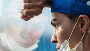 Gros plan sur une infirmière, masque sous le nez, qui regarde par une fenêtre, le bras et le front appuyés sur la vitre.