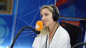Une femme blonde vêtue d'un chandail blanc regarde vers la gauche devant un micro orange dans un studio de radio bleu.