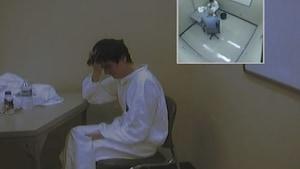 Image d'Alexandre Bissonnette tirée d'une caméra de surveillance. Il est assis sur une chaise, face à une table. Vêtu d'une combinaison blanche, il se prend la tête avec sa main droite. Dans le coin supérieur droit de l'image, on aperçoit une autre prise de vue de la caméra, en plongée. Le sergent enquêteur Steve Girard, de la Sûreté du Québec, fait face à Bissonnette.