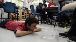 Un garçon couché sur le plancher de la classe participe à l'expérience scientifique.