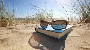 Une paire de lunette de soleil et un livre sur le sable d'une plage ensoleillée.