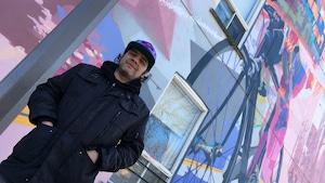 Samuel Médrano devant un mur coloré d'un bâtiment d'Hochelaga-Maisonneuve.