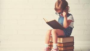 Un enfant lit un livre avec de grosses lunettes, assis sur plusieurs livres.