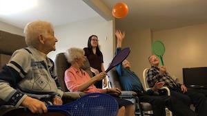 Des personnes âgées ont des raquettes à la main et tente de frapper un ballon d'anniversaire