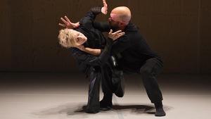 La danseuse tient une position accroupie en équilibre sur son partenaire masculin.