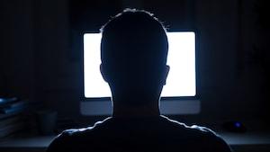 Silhouette de la tête d'un homme devant un écran d'ordinateur allumé.