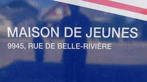 """Un panneau disant """"maison de jeunes, 9945 rue de Belle-Rivière""""."""