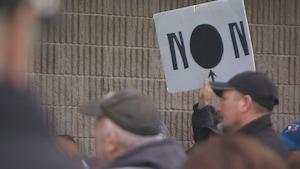 Quelqu'un tient une affiche NON avec le O remplacé par un point noir.