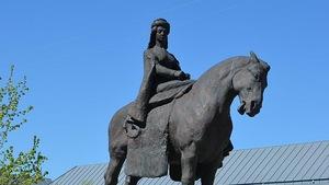 Une femme sur un cheval est montée sur un gros bloc de pierre.