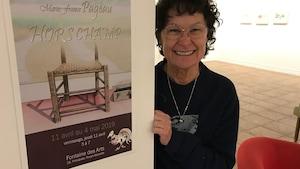 L'artiste Marie-France Pageau pose dans une salle lumineuse, devant l'affiche de son  exposition.