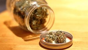 Un pot Masson renversé sur le côté avec de la marijuana à l'intérieur ainsi que dans le couvercle du pot, qui est ouvert et déposé sur une table.
