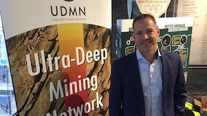 Patrice Dubreuil avec une bannière promotionnelle du Ultra-Deep Mining Network