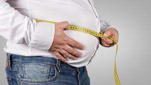 Un homme obèse mesure son tour de taille.