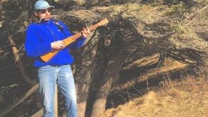 Entouré d'épinettes, Michael Saulnier joue sur une mini guitare et de l'harmonica.