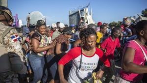 Groupe de citoyens haïtiens s'empressant de traverser la frontière, munis de marchandises, sous la supervision armée d'un soldat