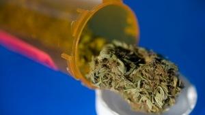 Du cannabis tombant d'un contenant pour médicaments.